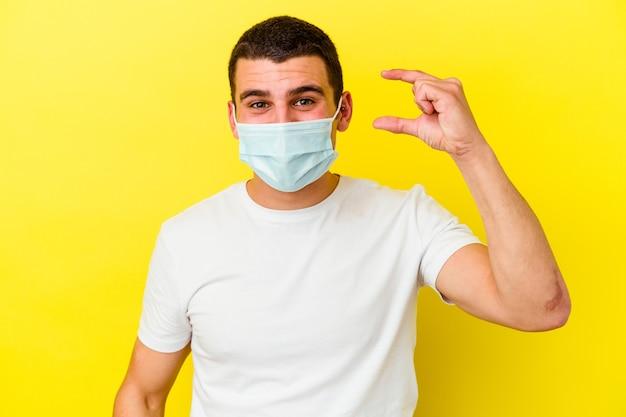 Giovane uomo caucasico che indossa una protezione per il coronavirus isolato su sfondo giallo che tiene qualcosa di piccolo con l'indice, sorridente e fiducioso.