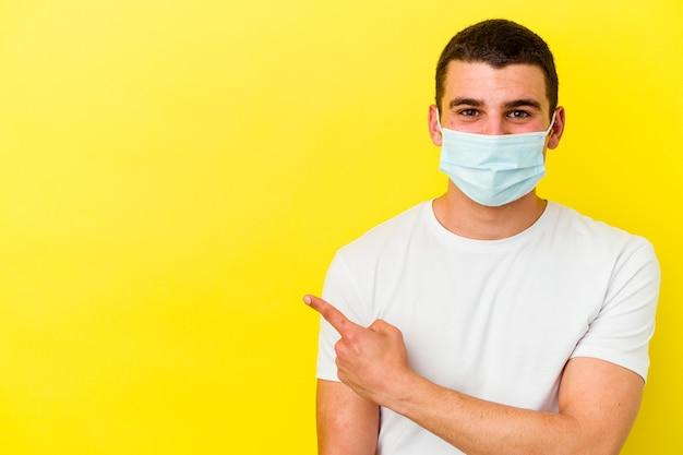 Giovane uomo caucasico che indossa una protezione per il coronavirus isolato su sfondo giallo sorridendo e indicando da parte, mostrando qualcosa in uno spazio vuoto.