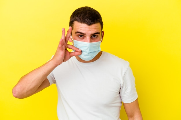 Giovane uomo caucasico che indossa una protezione per il coronavirus isolato su sfondo giallo con le dita sulle labbra che mantengono un segreto.
