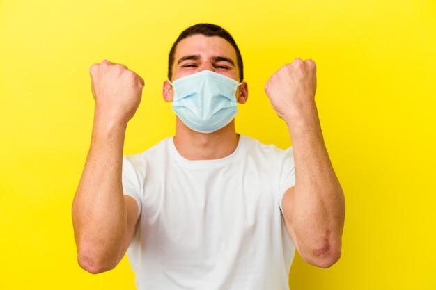 Giovane uomo caucasico che indossa una protezione per il coronavirus isolato sul muro giallo che esulta spensierato ed eccitato. concetto di vittoria.