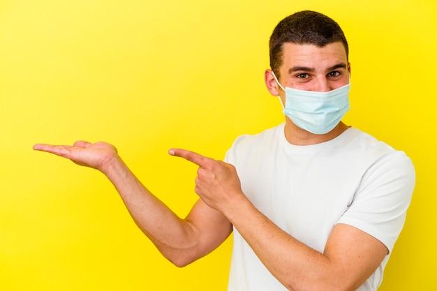 Il giovane uomo caucasico che indossa una protezione per il coronavirus isolato sulla parete gialla eccitato tenendo uno spazio della copia sul palmo