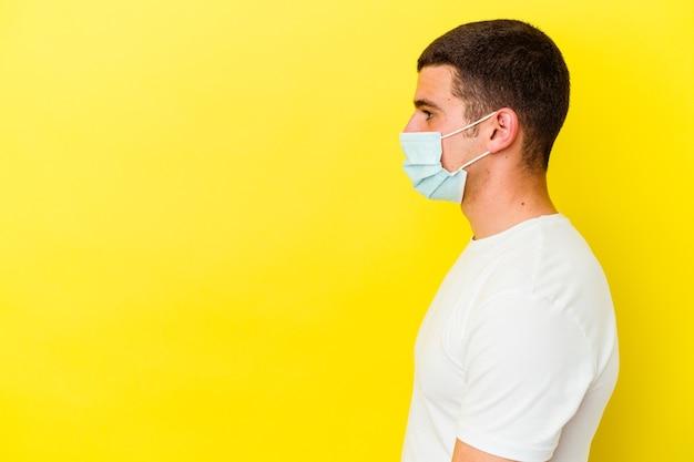 Giovane uomo caucasico che indossa una protezione per il coronavirus isolato sul muro giallo che guarda a sinistra, posa laterale.