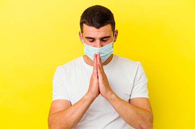 Il giovane uomo caucasico che indossa una protezione per il coronavirus isolato sul muro giallo tenendosi per mano in preghiera vicino alla bocca, si sente sicuro.
