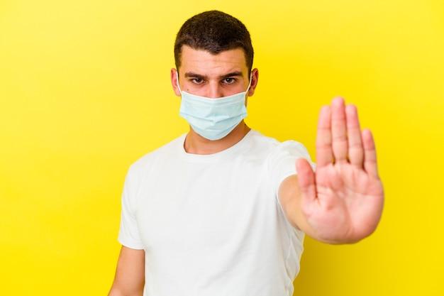 Giovane uomo caucasico che indossa una protezione per il coronavirus isolato sul muro giallo in piedi con la mano tesa che mostra il segnale di stop, impedendoti.