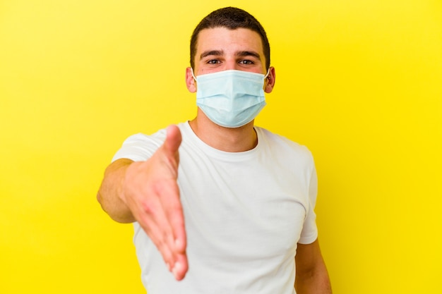 Giovane uomo caucasico che indossa una protezione per il coronavirus isolato sul muro giallo che allunga la mano alla macchina fotografica nel gesto di saluto.