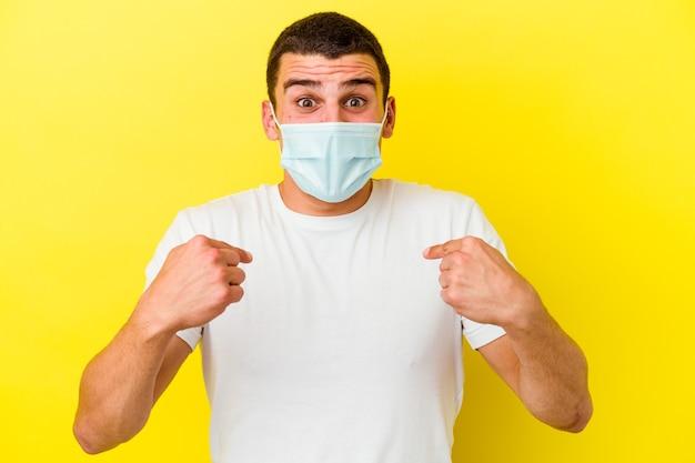 Giovane uomo caucasico che indossa una protezione per il coronavirus isolato sul muro giallo sorpreso indicando con il dito, sorridendo ampiamente.