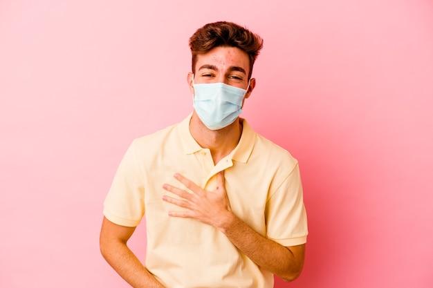 Il giovane uomo caucasico che indossa una protezione per il coronavirus sul rosa ride felice e si diverte a tenere le mani sullo stomaco.
