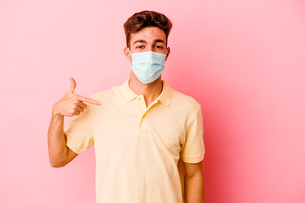 Giovane uomo caucasico che indossa una protezione per il coronavirus sulla persona rosa che indica a mano uno spazio di copia della maglietta, orgoglioso e fiducioso