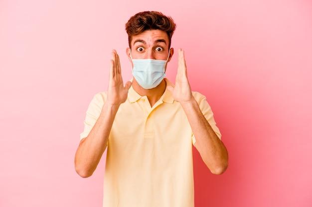 Giovane uomo caucasico che indossa una protezione per il coronavirus in rosa che grida eccitato al fronte.