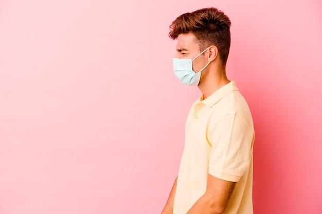 Giovane uomo caucasico che indossa una protezione per il coronavirus sul rosa che grida verso uno spazio di copia