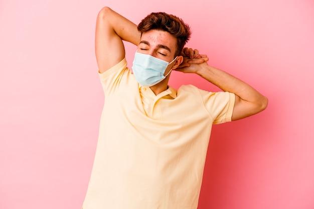 Giovane uomo caucasico che indossa una protezione per il coronavirus su braccia allungate rosa, posizione rilassata.