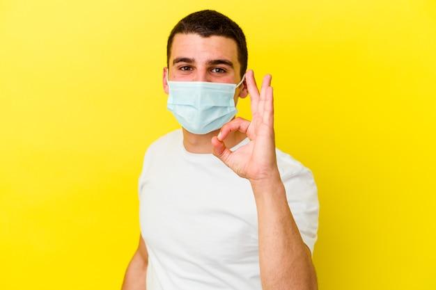 Giovane uomo caucasico che indossa una protezione per il coronavirus su giallo allegro e fiducioso che mostra gesto giusto.