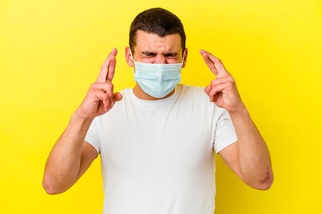 Giovane uomo caucasico che indossa una protezione per il coronavirus sulle dita incrociate gialle per avere fortuna
