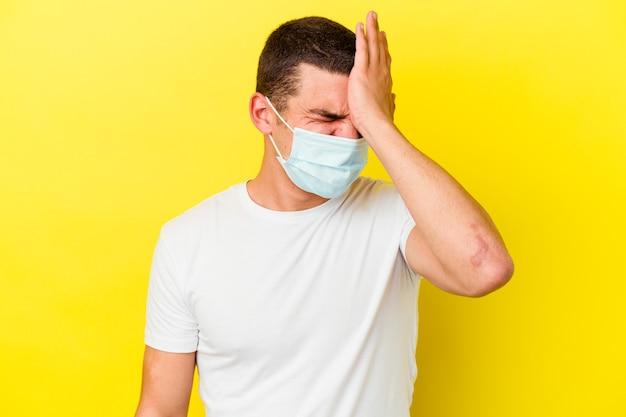 Giovane uomo caucasico che indossa una protezione per il coronavirus su giallo dimenticando qualcosa, schiaffeggiando la fronte con il palmo e chiudendo gli occhi.
