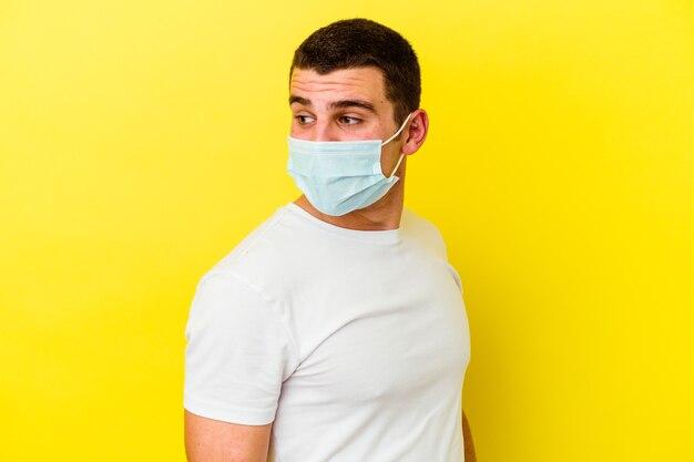 Il giovane uomo caucasico che indossa una protezione per il coronavirus sul giallo guarda da parte sorridente, allegro e piacevole.