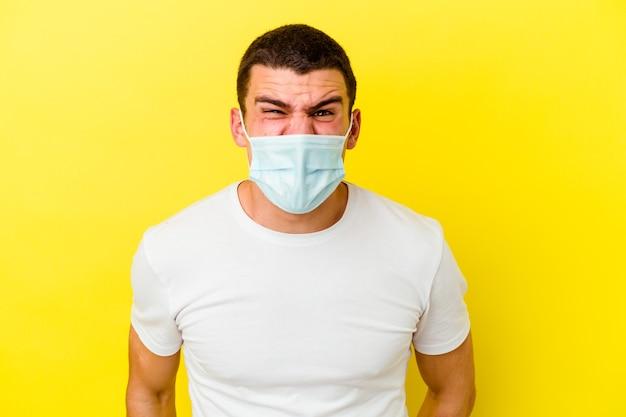 Giovane uomo caucasico che indossa una protezione per il coronavirus su giallo urlando molto arrabbiato e aggressivo.