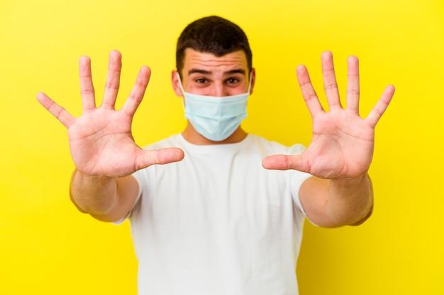 Giovane uomo caucasico che indossa una protezione per il coronavirus su giallo che mostra il numero dieci con le mani.