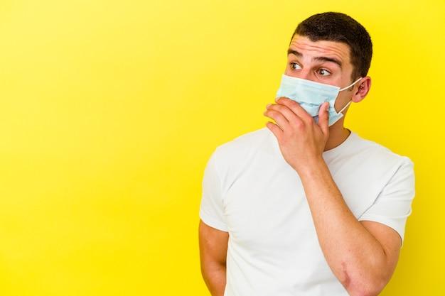 Giovane uomo caucasico che indossa una protezione per il coronavirus su giallo premuroso guardando uno spazio di copia che copre la bocca con la mano.