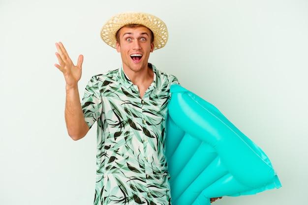 Giovane uomo caucasico che indossa abiti estivi e tiene in mano un materasso ad aria isolato su sfondo bianco riceve una piacevole sorpresa, eccitato e alzando le mani.