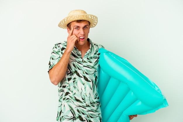 Giovane uomo caucasico che indossa abiti estivi e tiene in mano un materasso ad aria isolato su sfondo bianco che mostra un gesto di delusione con l'indice.