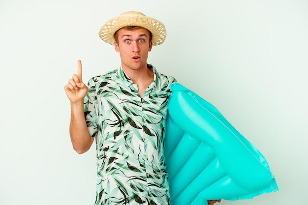 Giovane uomo caucasico che indossa abiti estivi e tiene in mano un materasso ad aria isolato su bianco con qualche grande idea, concetto di creatività.
