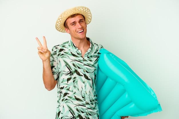 Giovane uomo caucasico che indossa abiti estivi e tiene in mano un materasso ad aria isolato su bianco gioioso e spensierato che mostra un simbolo di pace con le dita.