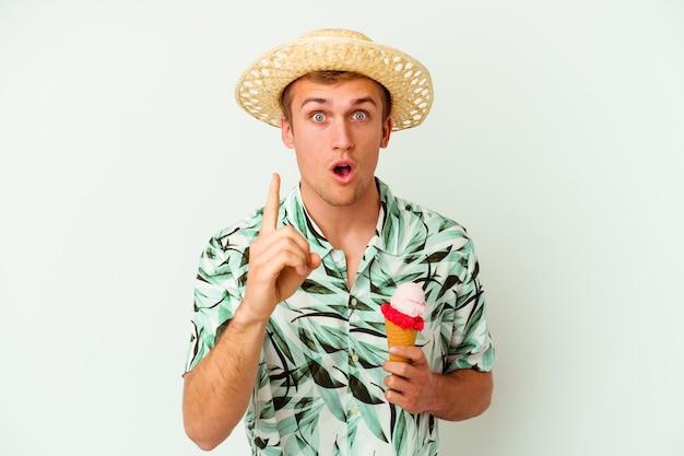 Giovane uomo caucasico che indossa abiti estivi e tiene in mano un gelato isolato su sfondo bianco con un'idea, un concetto di ispirazione.