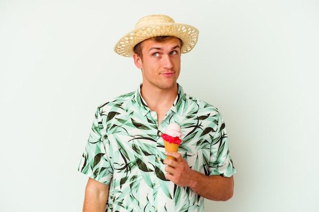Giovane uomo caucasico che indossa abiti estivi e tiene in mano un gelato isolato su bianco sognando di raggiungere obiettivi e scopi