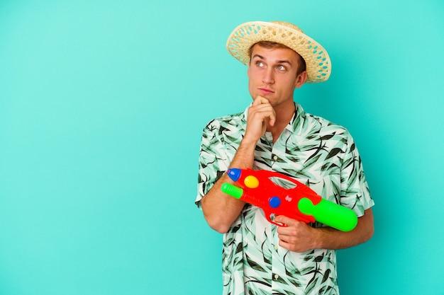Giovane uomo caucasico che indossa abiti estivi e tiene in mano una pistola ad acqua isolata su sfondo bianco guardando di traverso con espressione dubbiosa e scettica.