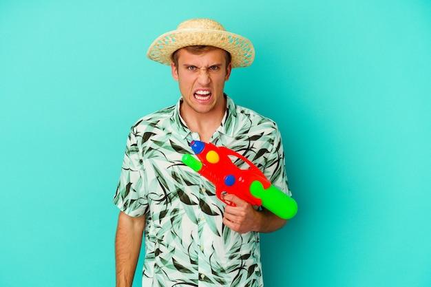 Giovane uomo caucasico che indossa abiti estivi e tiene in mano una pistola ad acqua isolata su sfondo bianco urlando molto arrabbiato e aggressivo.
