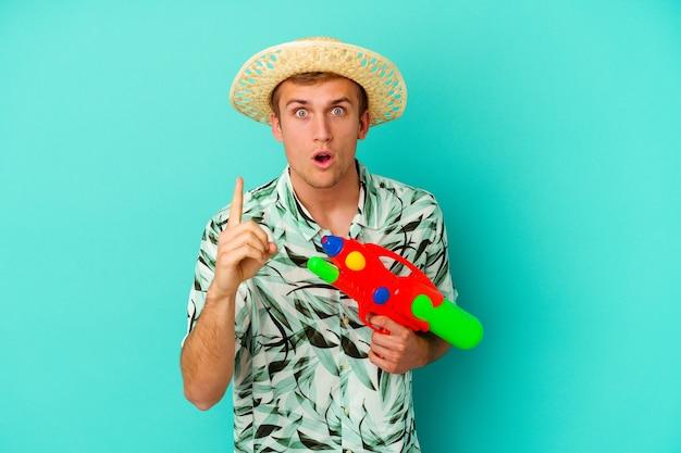 Giovane uomo caucasico che indossa abiti estivi e tiene in mano una pistola ad acqua isolata su bianco che ha un'idea, un concetto di ispirazione.