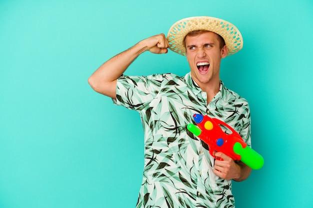 Giovane uomo caucasico che indossa abiti estivi e tiene in mano una pistola ad acqua isolata su bianco alzando il pugno dopo una vittoria, concetto vincitore.