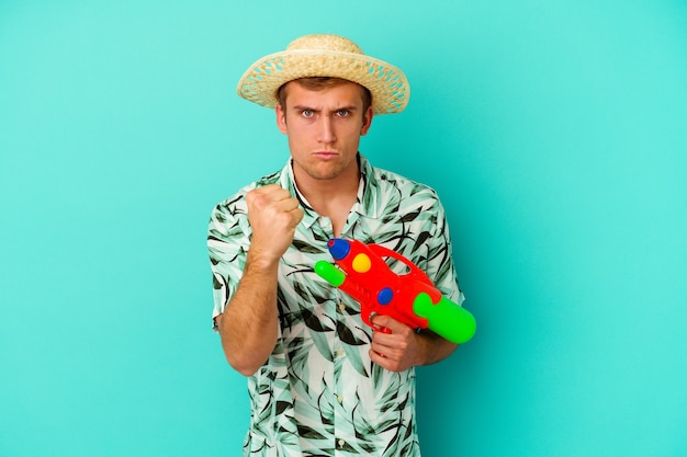 Giovane uomo caucasico che indossa abiti estivi e tiene in mano una pistola ad acqua isolata su bianco che mostra pugno, espressione facciale aggressiva.