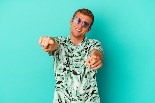 Giovane uomo caucasico che indossa abiti estivi isolati su sfondo blu sorrisi allegri che puntano verso la parte anteriore.