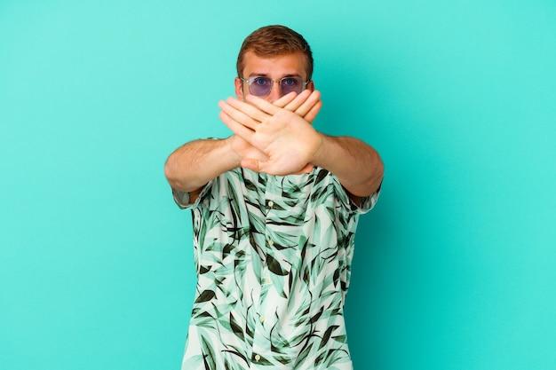 Giovane uomo caucasico che indossa abiti estivi isolati sulla parete blu facendo un gesto di diniego