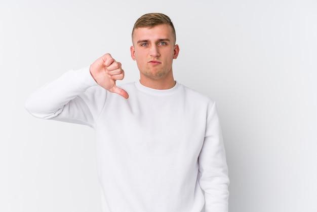 Giovane uomo caucasico su bianco che mostra un gesto di avversione, pollice in giù. concetto di disaccordo.