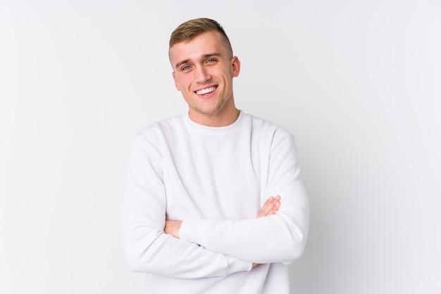 Giovane uomo caucasico su bianco che si sente fiducioso, incrociando le braccia con determinazione.