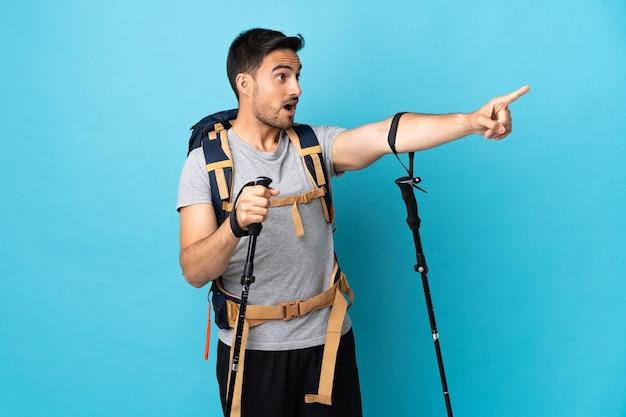 Giovane uomo caucasico con zaino e bastoncini da trekking isolati su sfondo blu che punta lontano