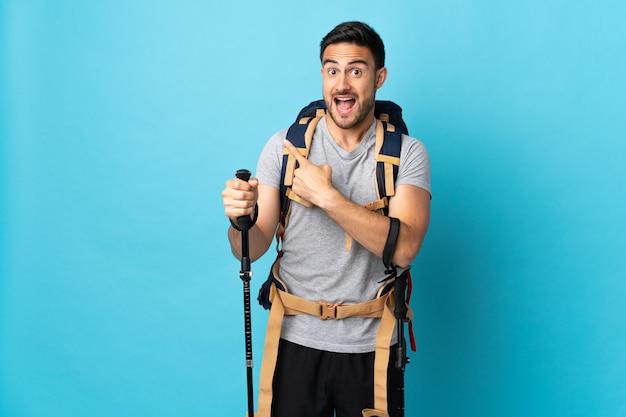 Giovane uomo caucasico con zaino e bastoncini da trekking isolati su sfondo blu sorpreso e rivolto verso il lato