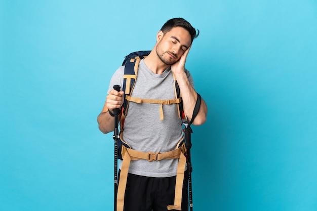 Giovane uomo caucasico con zaino e bastoncini da trekking isolati sulla parete blu che fa gesto di sonno nell'espressione dorable