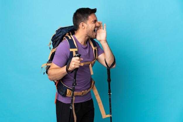 Giovane uomo caucasico con zaino e bastoncini da trekking isolati sulla parete blu che grida con la bocca spalancata di lato