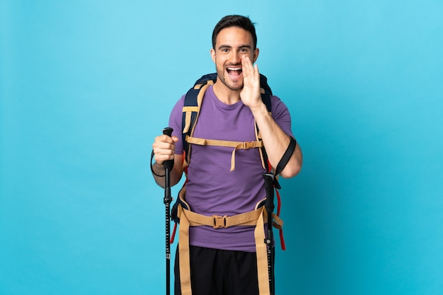 Giovane uomo caucasico con zaino e bastoncini da trekking isolati sulla parete blu che grida con la bocca spalancata