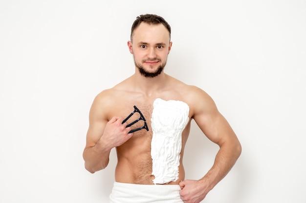 Il giovane uomo caucasico con la barba tiene il rasoio rade il petto con schiuma da barba bianca su sfondo bianco. uomo che si rade il busto