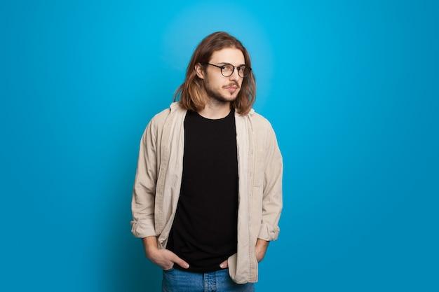 Il giovane uomo caucasico con barba e capelli lunghi con gli occhiali sta guardando con fiducia
