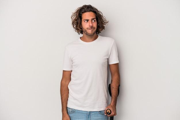 Il giovane uomo caucasico con le stampelle isolato su sfondo grigio confuso, si sente dubbioso e insicuro.