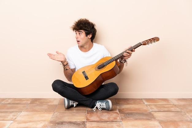Giovane uomo caucasico con una chitarra che si siede sul pavimento con espressione facciale di sorpresa