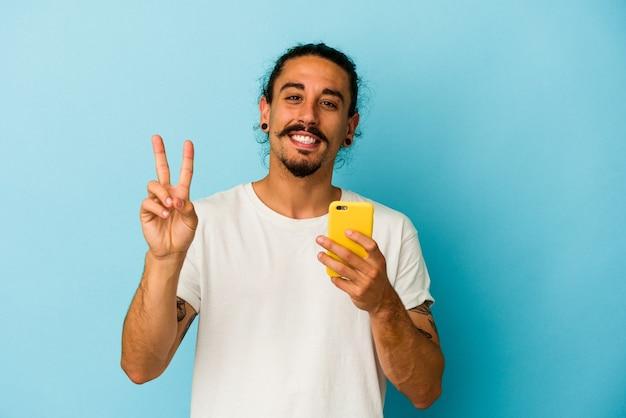 Giovane uomo caucasico con i capelli lunghi che tiene il telefono cellulare isolato su sfondo blu gioioso e spensierato che mostra un simbolo di pace con le dita.