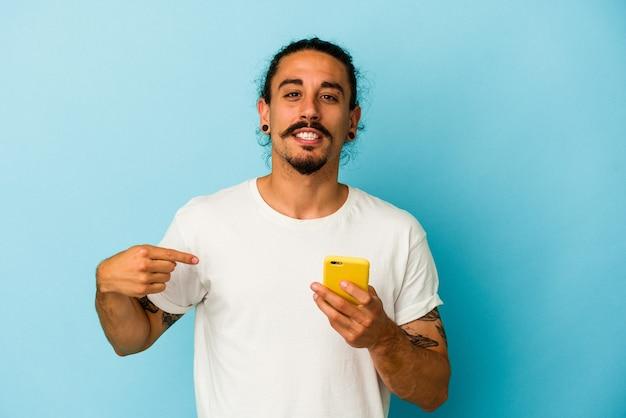Giovane uomo caucasico con i capelli lunghi che tiene il telefono cellulare isolato su sfondo blu persona che indica a mano uno spazio copia camicia, orgoglioso e fiducioso