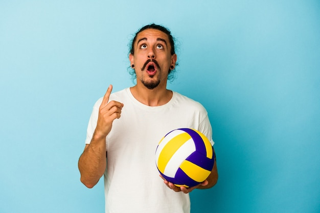 Giovane uomo caucasico con i capelli lunghi isolato su sfondo blu che punta al rialzo con la bocca aperta.