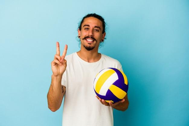 Giovane uomo caucasico con capelli lunghi isolato su sfondo blu che mostra il numero due con le dita.